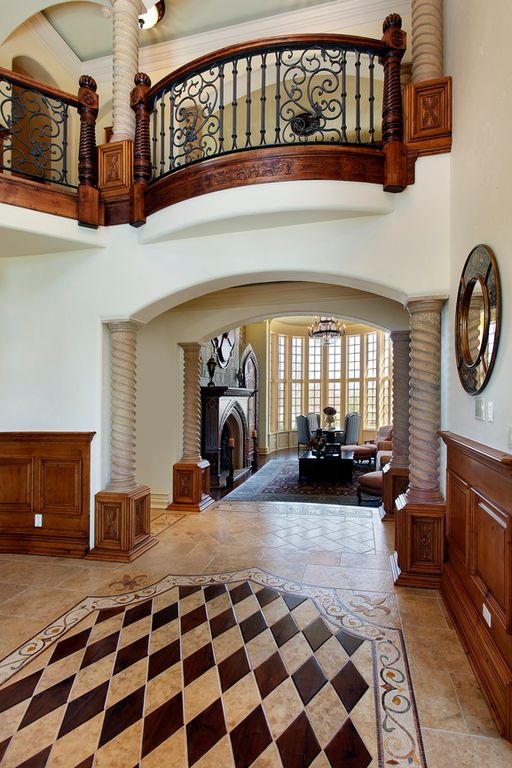 Traditional Entryway with High ceiling, simple marble tile floors, Balcony, Columns, stone tile floors, Wainscotting