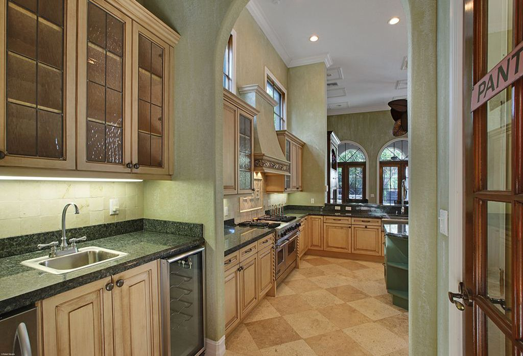 Mediterranean Kitchen with Stone Tile, Ivory honed travertine wall tile, Custom hood, Limestone Tile, Kitchen island, Flush