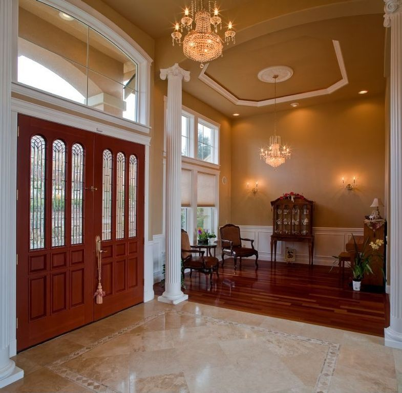 Traditional Entryway with Chandelier, Columns, Arched window, Transom window, Glass panel door, High ceiling