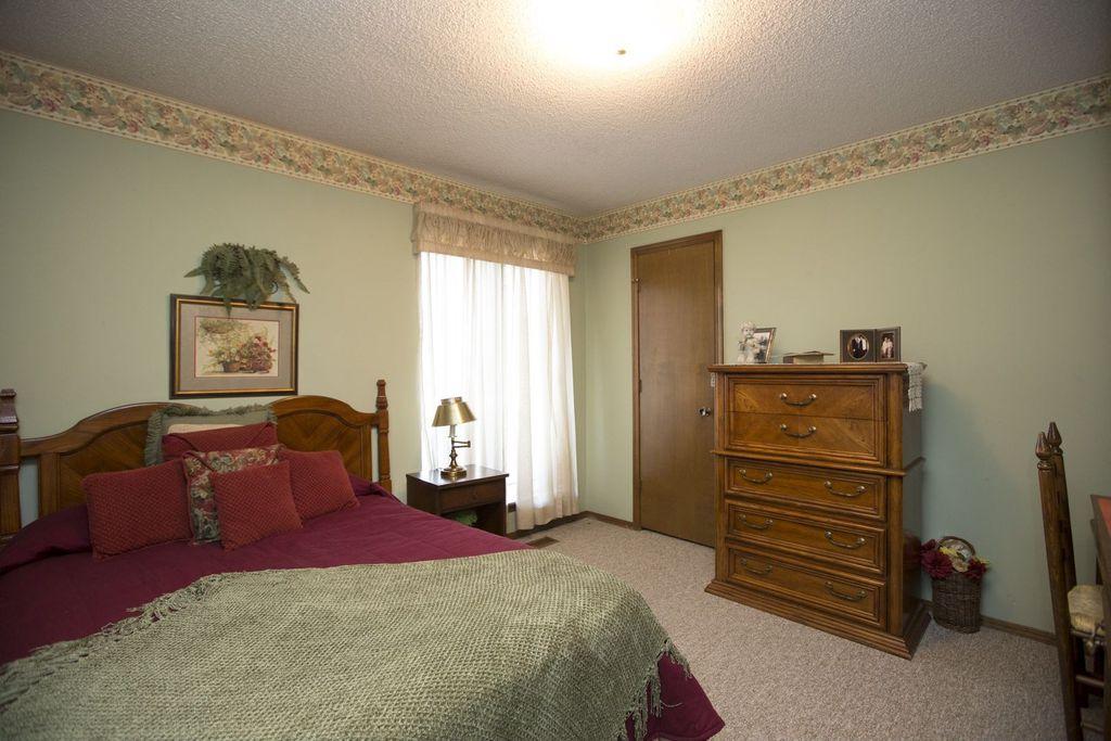 Craftsman Guest Bedroom with Built-in bookshelf, interior wallpaper, Carpet, flush light