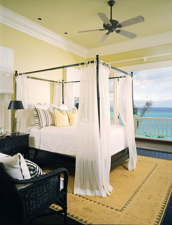 Tropical Guest Bedroom with Standard height, Crown molding, Black wicker arm chair, picture window, Ceiling fan, Paint