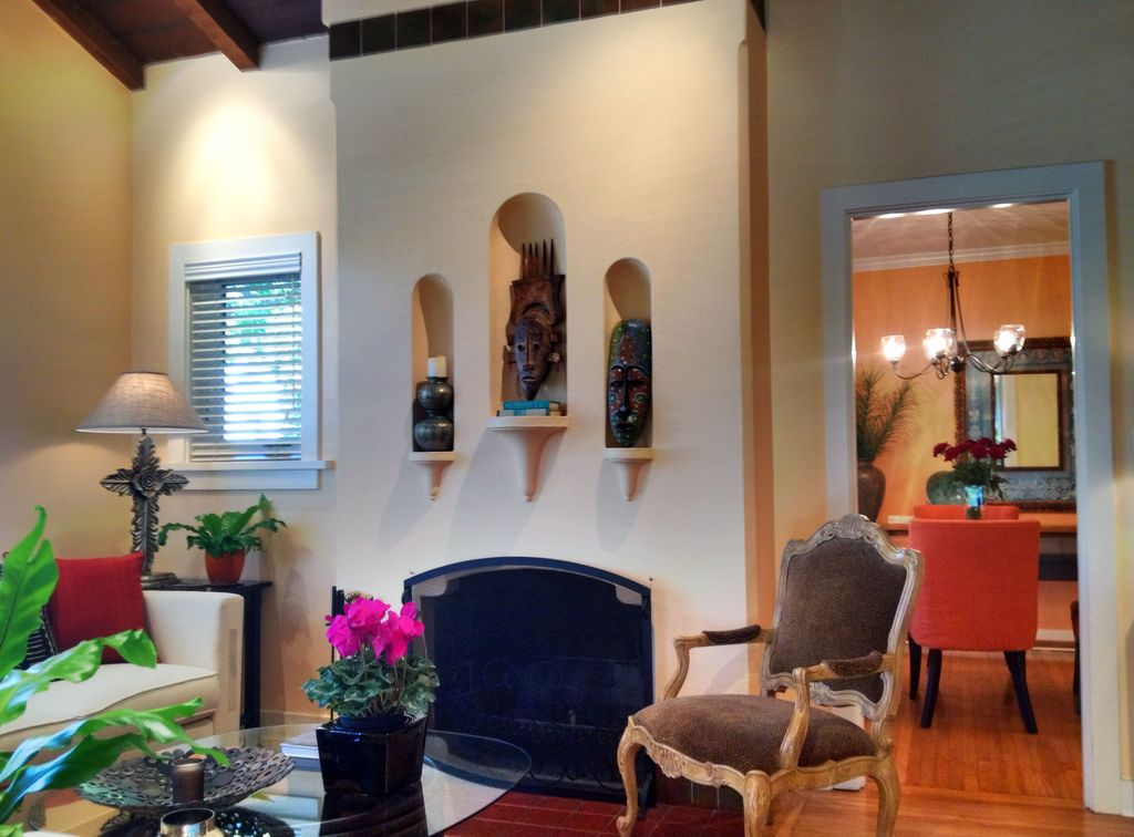 Eclectic Living Room with Built-in bookshelf, Standard height, insert fireplace, Hardwood floors, Exposed beam, Casement