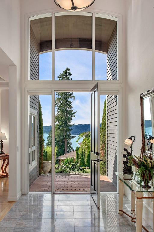 Contemporary Entryway with High ceiling, picture window, simple marble floors, specialty door, Pendant light