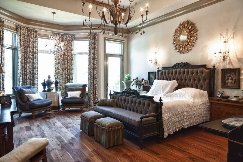 Traditional Master Bedroom with High ceiling, specialty window, French doors, Wood and iron chandelier, Dark hardwood floors