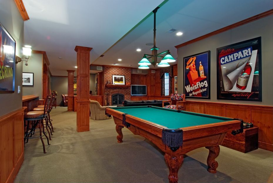 Craftsman Game Room with Wainscotting, Chair rail, Carpet, can lights, Crown molding, Columns, Standard height, Pendant light