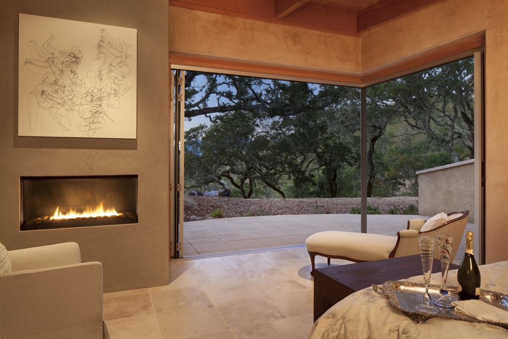 Contemporary Master Bedroom with Fireplace, sandstone floors, insert fireplace, Standard height, Exposed beam, folding door