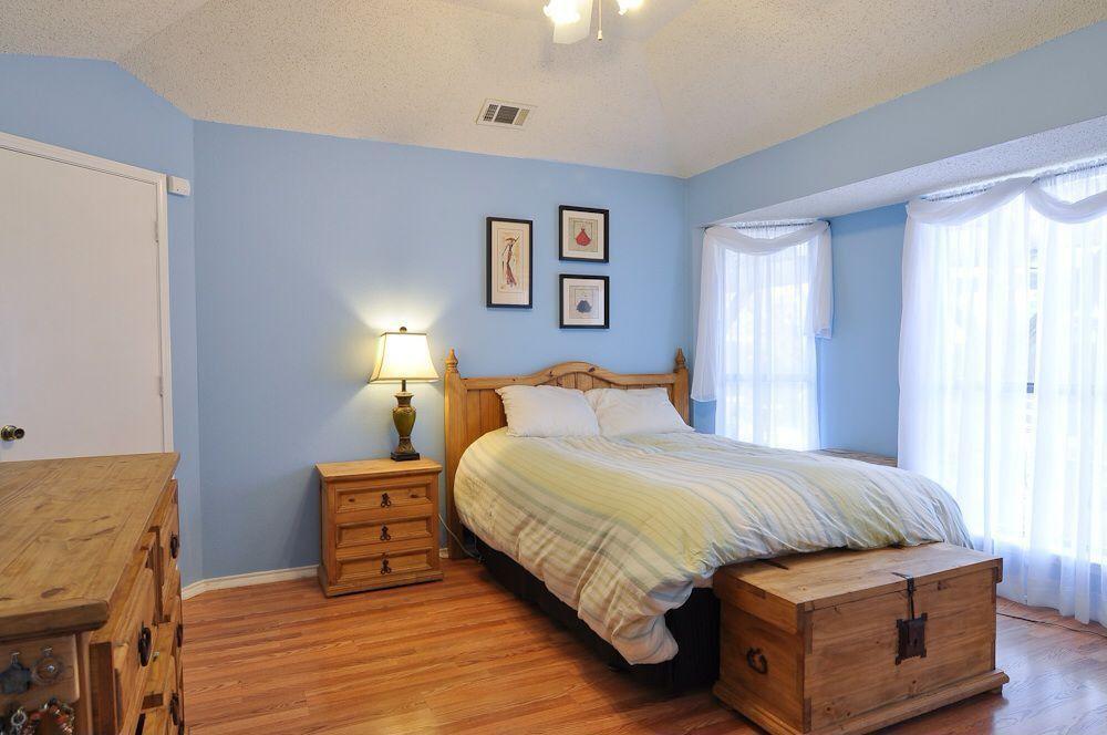 Cottage Guest Bedroom with double-hung window, flat door, Ceiling fan, Standard height, Hardwood floors