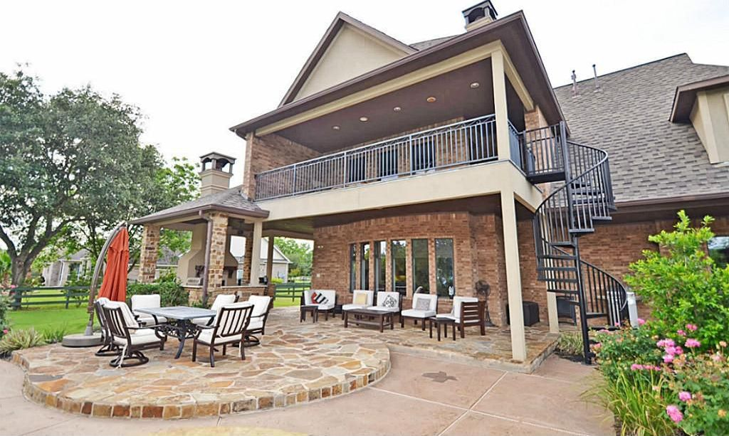 Traditional Patio with exterior stone floors, picture window, Fence, Deck Railing, outdoor pizza oven
