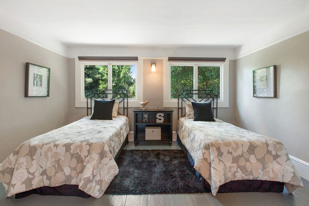 Contemporary Guest Bedroom with Hardwood floors, Wall sconce, Crown molding
