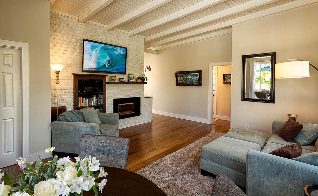 Contemporary Living Room with Standard height, Built-in bookshelf, six panel door, Fireplace, Hardwood floors, Exposed beam