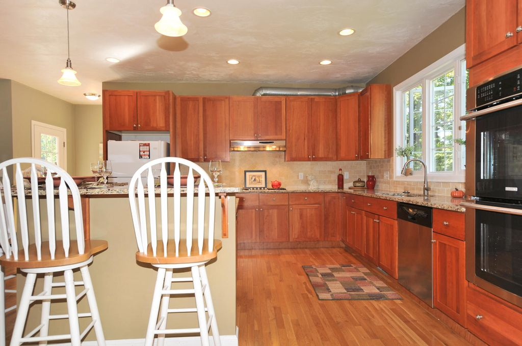 Craftsman Kitchen with Kitchen island, L-shaped, Breakfast bar, European Cabinets, Limestone Tile, Undermount sink, Flush