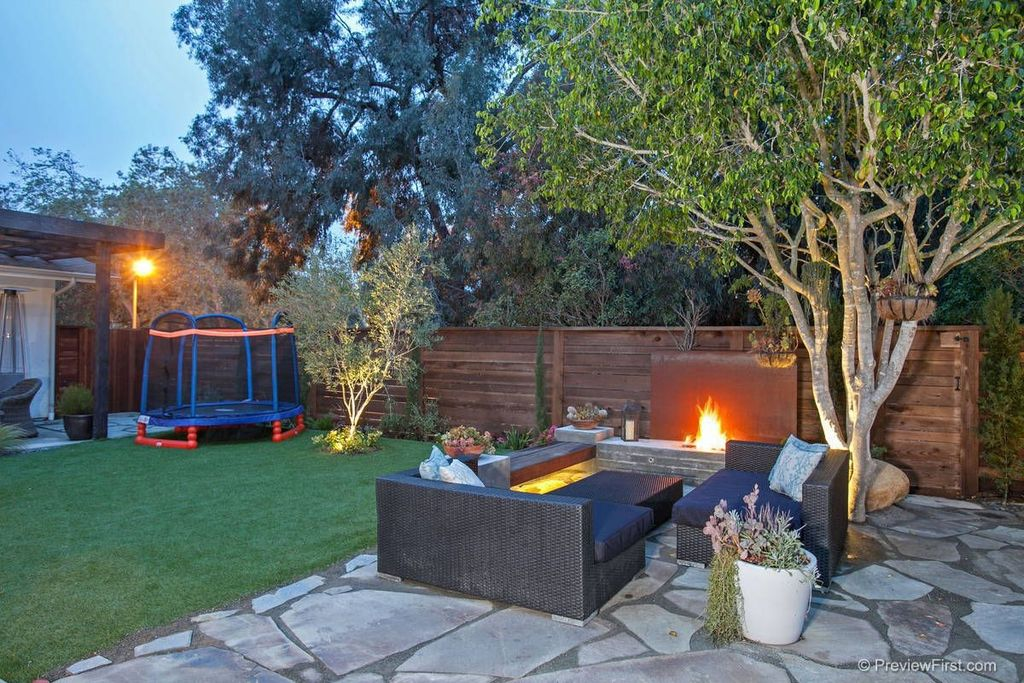Contemporary Patio with Fence, exterior stone floors, Fire pit, Trellis