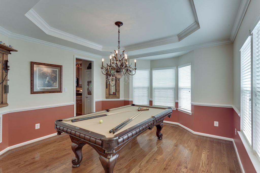 Traditional Game Room with Chair rail, Standard height, Crown molding, Hardwood floors, double-hung window, Chandelier