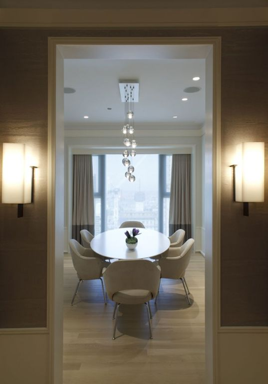 Contemporary Dining Room with Crown molding, Laminate floors, Wall sconce, Chandelier