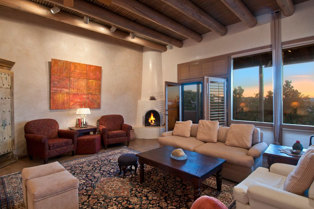 Mediterranean Living Room with Slip covered casual sofa, Exposed beam, Transom window, Club chair, Paint 1, Fireplace