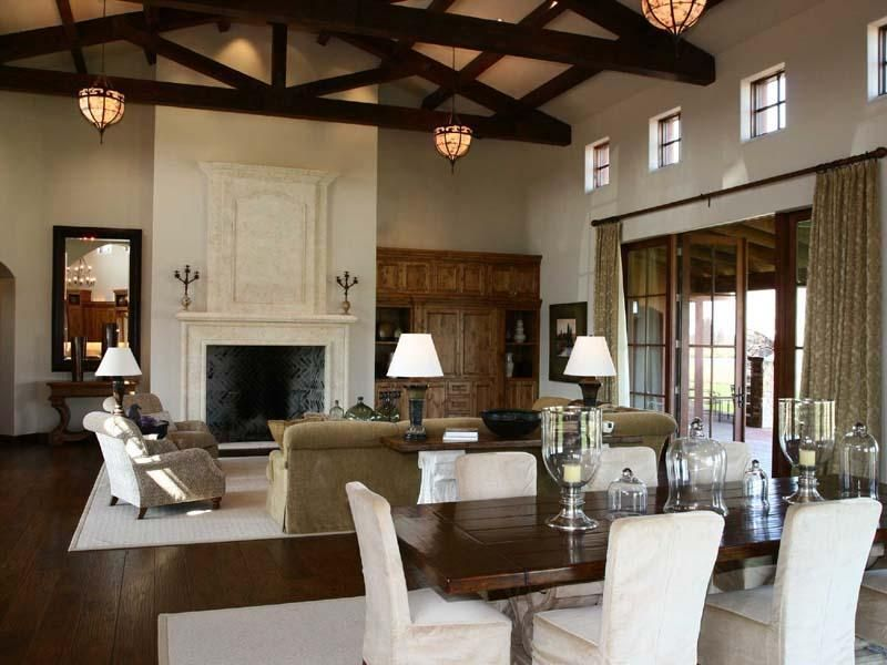 Traditional Great Room with Exposed beam, Built-in bookshelf, High ceiling, Chandelier, French doors, Cement fireplace