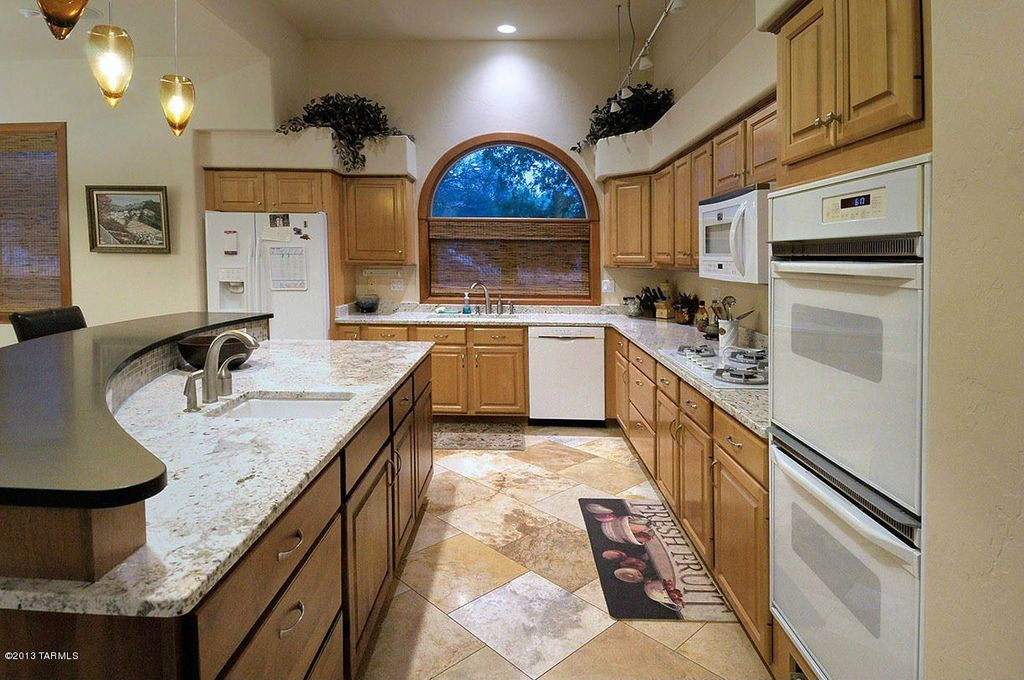 Traditional Kitchen with Built In Refrigerator, flush light, Standard height, stone tile floors, Kitchen island, Raised panel