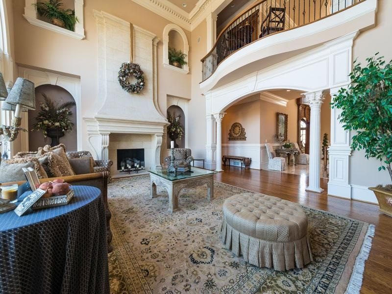 Traditional Living Room with Hardwood floors, can lights, Cathedral ceiling, Fireplace, Columns, Tufted ottoman by zentique