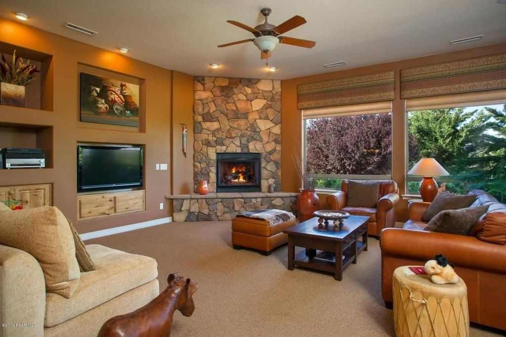 Rustic Living Room with can lights, Carpet, River rock stone fireplace, Mountain lodge drum end table, Standard height