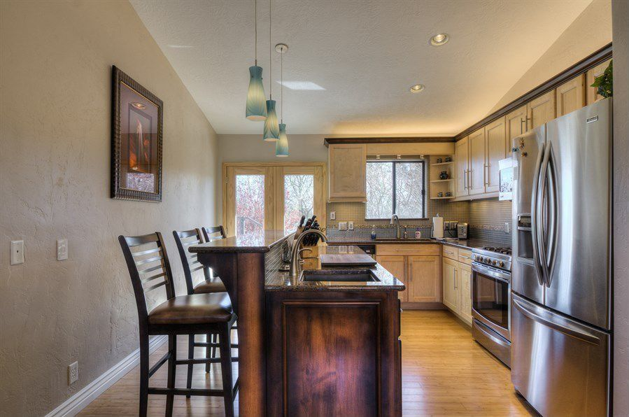 Craftsman Kitchen with Simple granite counters, Pendant light, European Cabinets, can lights, Multiple Refrigerators, Flush