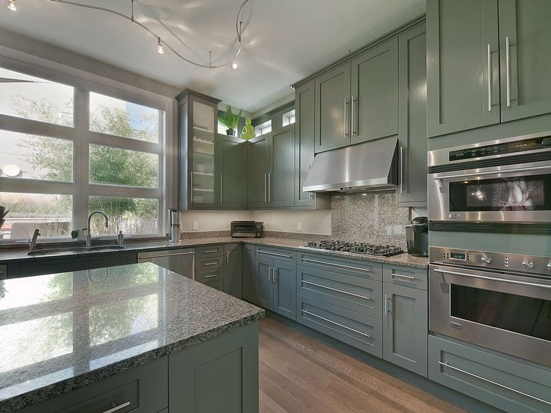 Contemporary Kitchen with Simple granite counters, Casement, double wall oven, can lights, two dishwashers, Glass panel