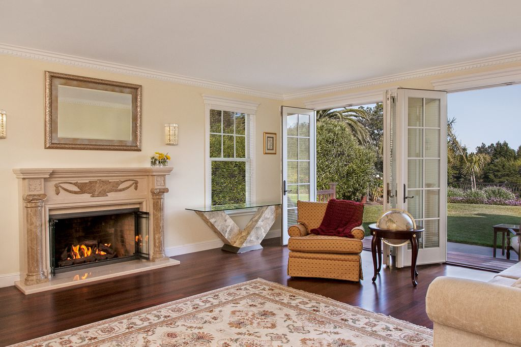 Traditional Living Room with double-hung window, Standard height, French doors, Crown molding, Fireplace, Hardwood floors