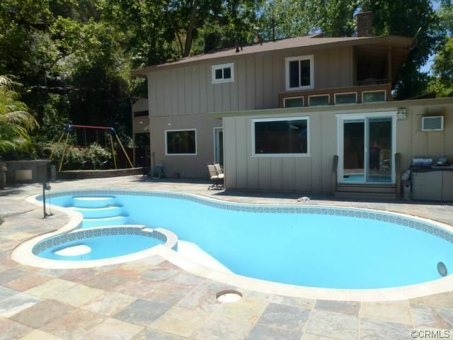 Traditional Swimming Pool with sliding glass door, exterior stone floors, Pool with hot tub, Raised beds, Outdoor kitchen