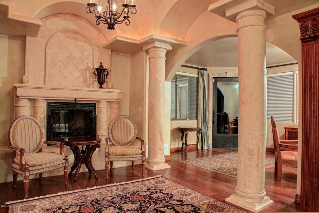 Mediterranean Living Room with Fireplace, stone fireplace, High ceiling, Hardwood floors, Chandelier, Columns