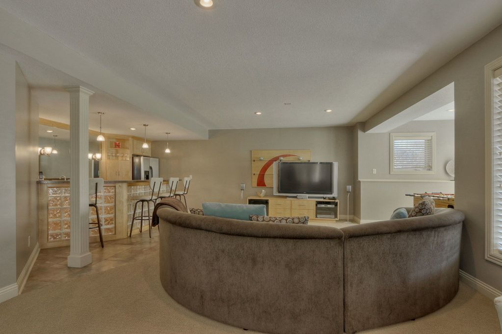 Contemporary Basement with limestone floors, Pendant light, can lights, Wall sconce, Exposed beam, Built-in bookshelf
