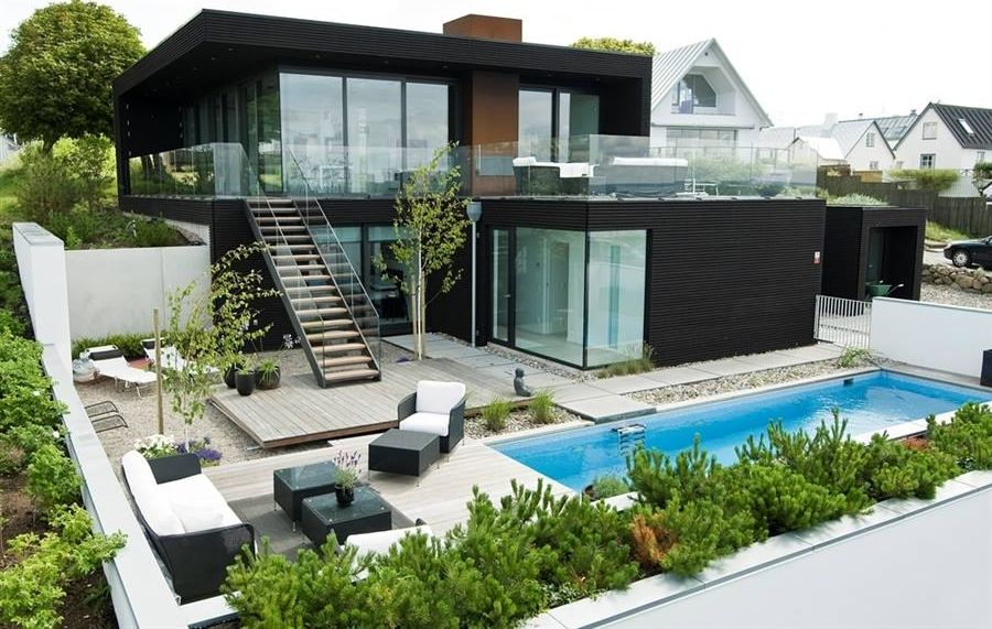 Modern Exterior of Home with Glass panel railing, Outdoor lounge chairs, Cement wall, picture window, Small rock ground cover