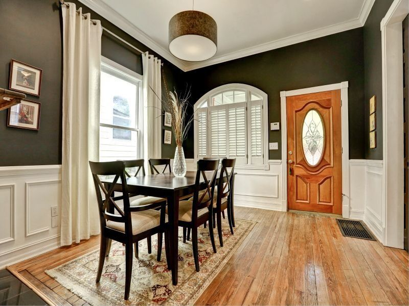 Traditional Dining Room with Wainscotting, Hardwood floors, Crown molding, Arched window, Glass panel door, Pendant light