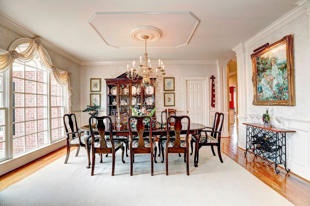 Traditional Dining Room with Hardwood floors, Built-in bookshelf, Standard height, picture window, six panel door, Chair rail