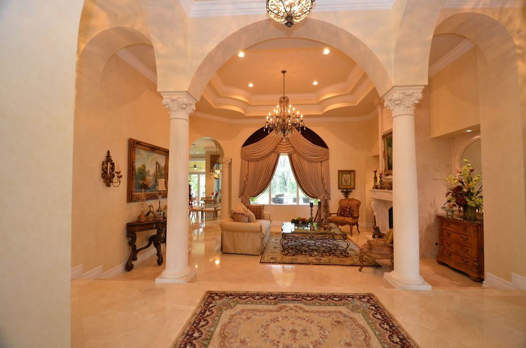 Mediterranean Entryway with sandstone floors, Standard height, Crown molding, Columns, Chandelier