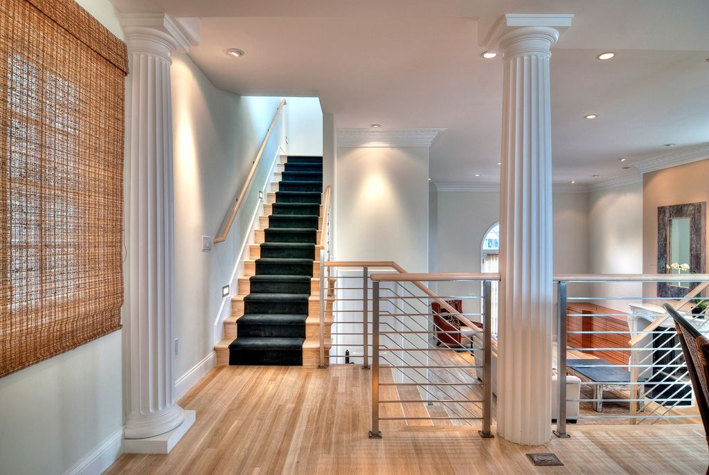 Modern Staircase with can lights, Wall sconce, curved staircase, Columns, Standard height, Hardwood floors