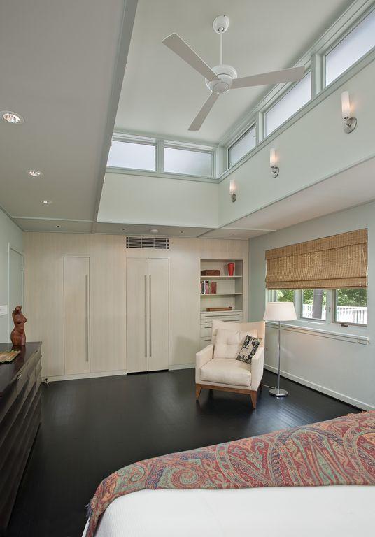 Modern Master Bedroom with High ceiling, Casement, Hardwood floors, Wall sconce, can lights, Ceiling fan, Built-in bookshelf