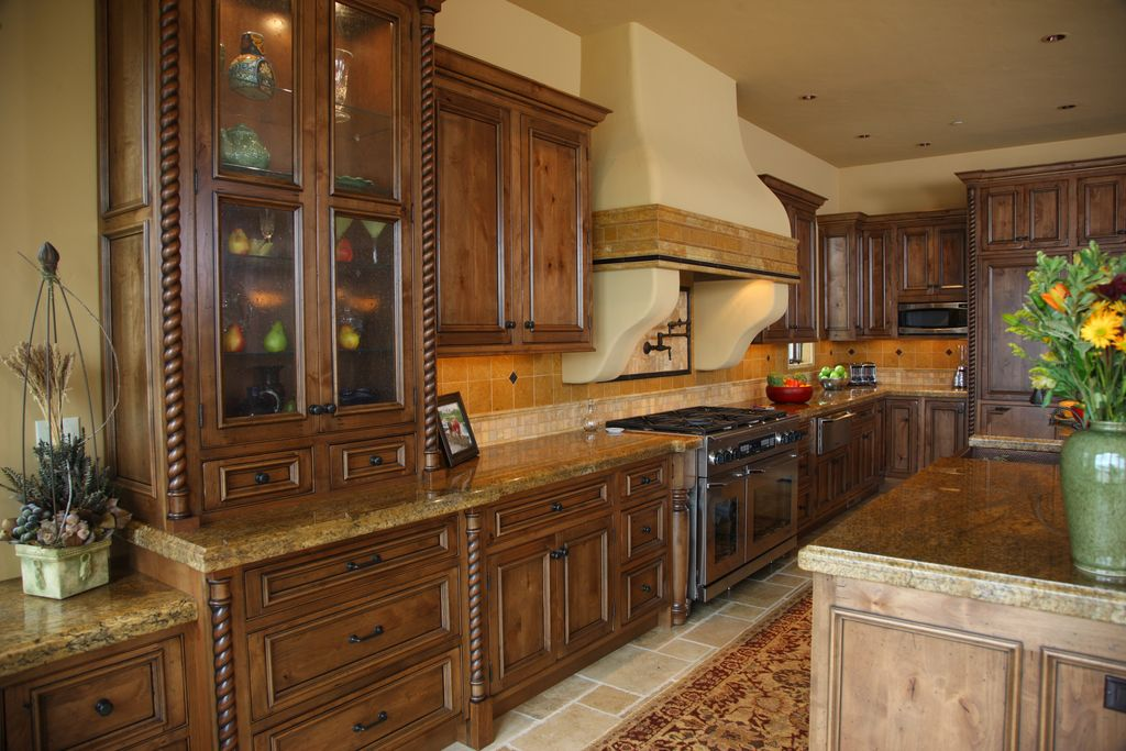 Mediterranean Kitchen with Framed Partial Panel, Standard height, built-in microwave, can lights, Complex granite counters