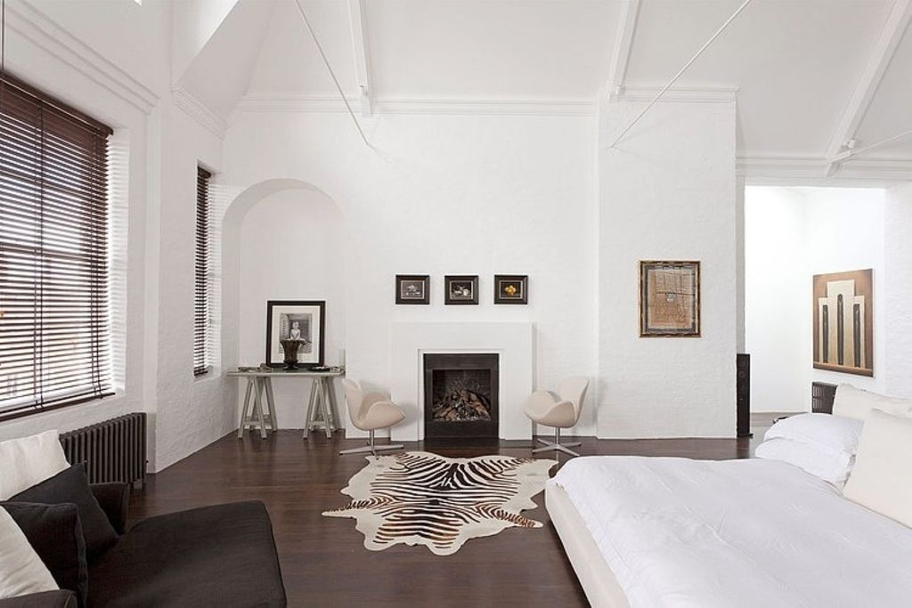 Modern Master Bedroom with Zebra printed cow hide rug, Paint, Sawhorse writing desk, Swan chair