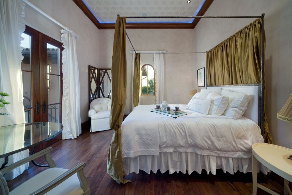 Mediterranean Guest Bedroom with can lights, High ceiling, Crown molding, Hardwood floors, French doors, Arched window