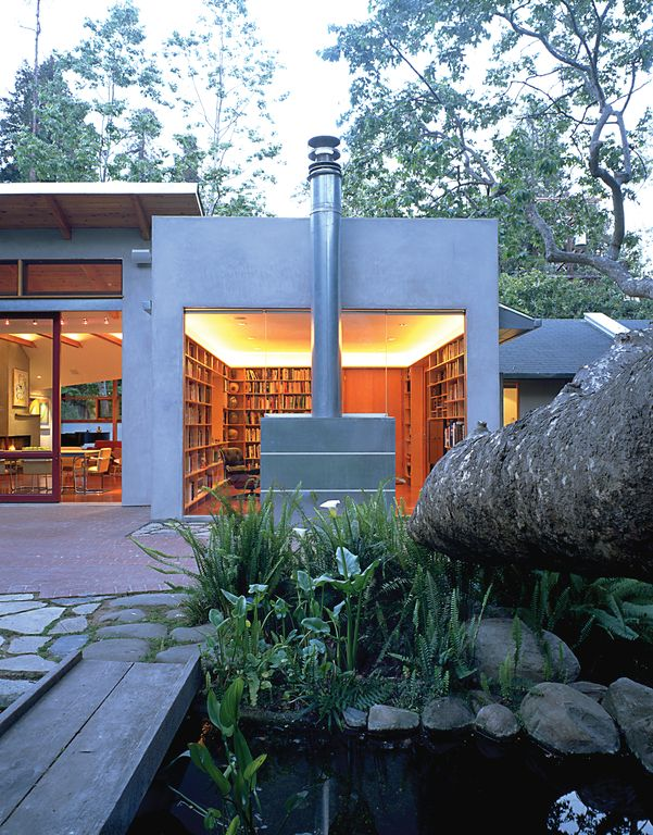 Contemporary Library with exterior stone floors, Eames lounge and ottoman, sliding glass door, Indoor/outdoor living