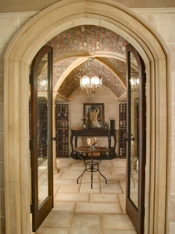 Mediterranean Wine Cellar with interior brick, French doors, Chandelier, Concrete tile , Crown molding, Columns, Exposed beam