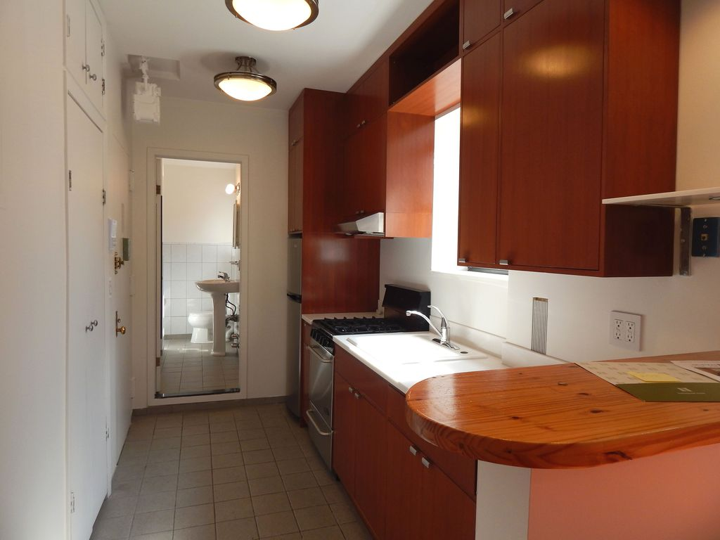 Contemporary Kitchen with Wood counters, Corian counters, gas range, Standard height, Galley, European Cabinets, flat door