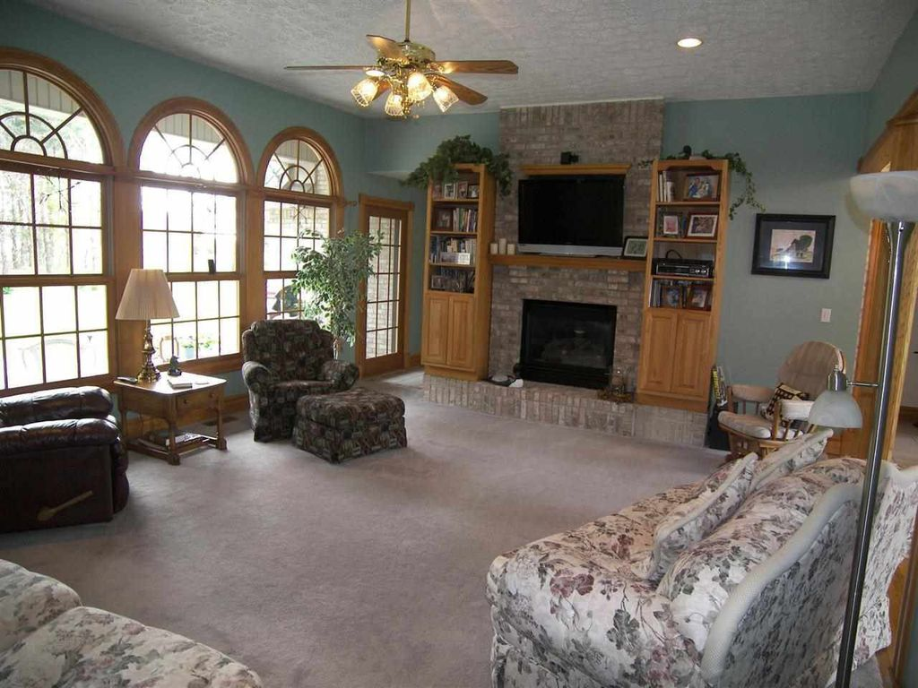 Traditional Living Room with Fireplace, can lights, Built-in bookshelf, Arched window, Carpet, Standard height, Ceiling fan