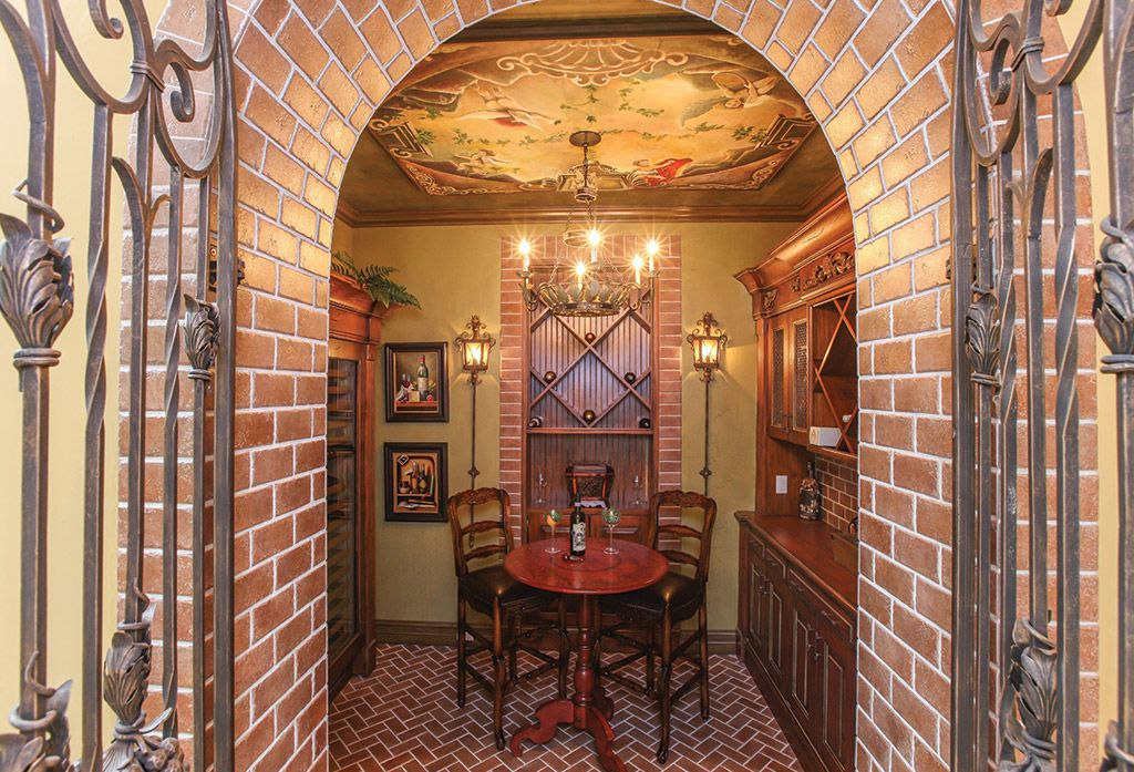 Traditional Wine Cellar with herringbone tile floors, Chandelier, Standard height, interior brick, Crown molding, Wall sconce