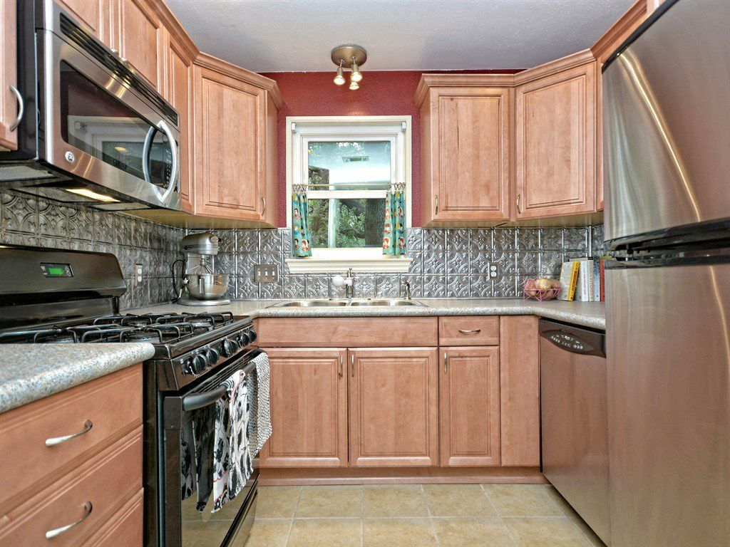 Country Kitchen with Metal Tile, Standard height, Raised panel, U-shaped, dishwasher, flush light, stone tile floors, Flush