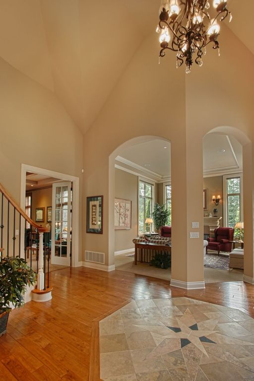 Traditional Entryway with High ceiling, Hardwood floors, Chandelier, French doors, Columns