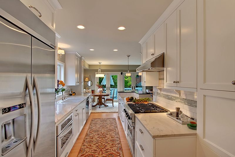 Traditional Kitchen with gas range, Complex marble counters, can lights, Galley, Flat panel cabinets, wall oven, dishwasher