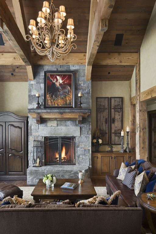 Rustic Living Room with Chandelier, Emerald pine square cocktail table, Columns, stone fireplace, Hardwood floors