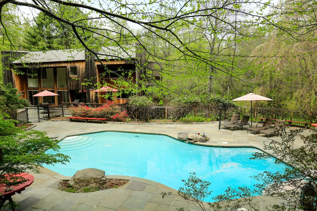 Rustic Swimming Pool with exterior stone floors, Raised beds, Fence, Pathway, Pool with hot tub
