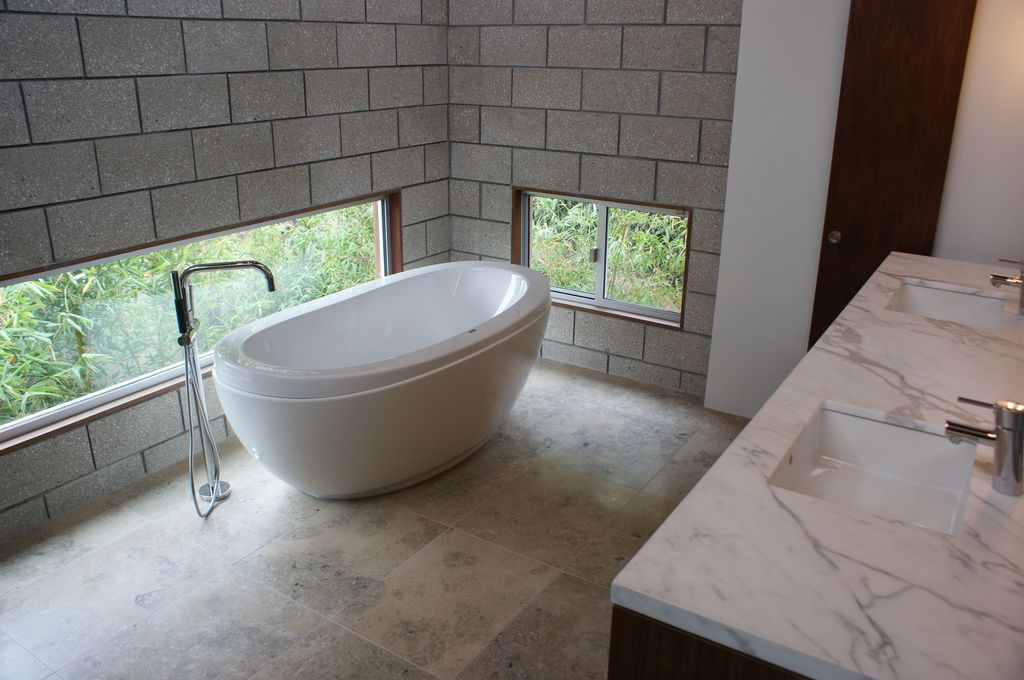 Contemporary Master Bathroom with Complex marble counters, picture window, stone tile floors, Bathtub, Double sink