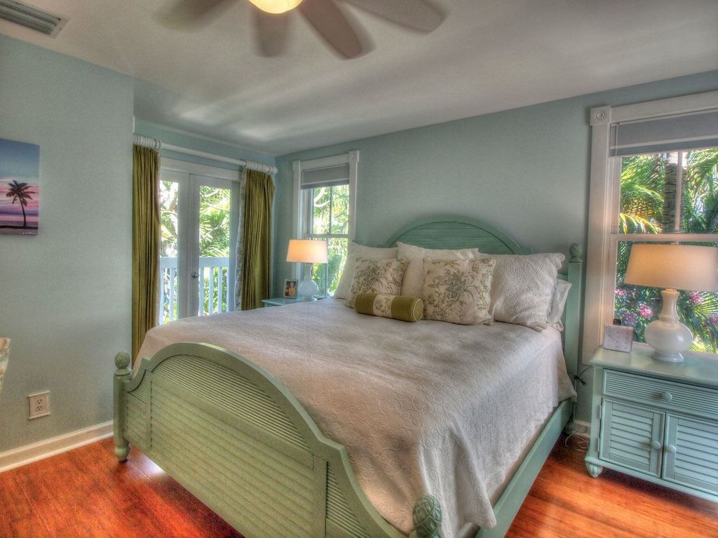 Cottage Guest Bedroom with Standard height, double-hung window, French doors, Hardwood floors, Ceiling fan
